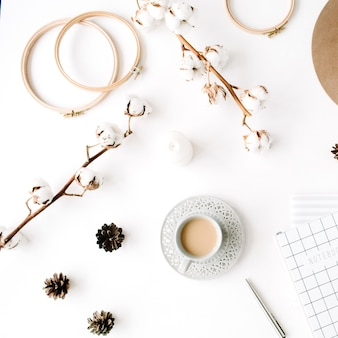 Arrangement d'accessoires féminins créatifs à la mode à plat avec café, branche de coton et agenda. chapeau, branche de coton, cahier, tasse à café, pomme de sapin, clips dorés sur blanc
