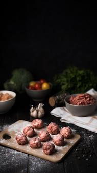 Arrangement d'angle élevé de boulettes de viande sur planche de bois
