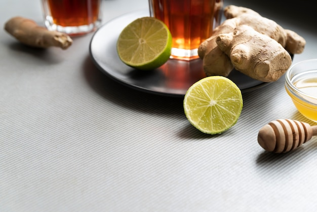 Arrangement à angle élevé avec du thé dans des verres et des tranches de citron vert
