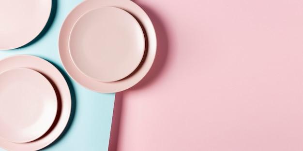 Arrangement d'assiettes roses avec espace copie