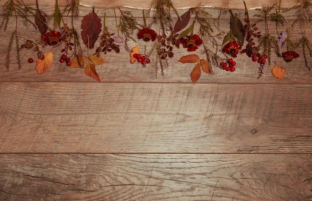 Arrangement d'automne de feuilles colorées et de fleurs d'automne sur un fond en bois avec un espace libre pour le texte. vue de dessus, concept de saison, effet rétro tonique, mise à plat