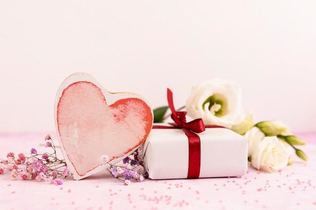 Arrangement avec biscuit en forme de coeur et cadeau
