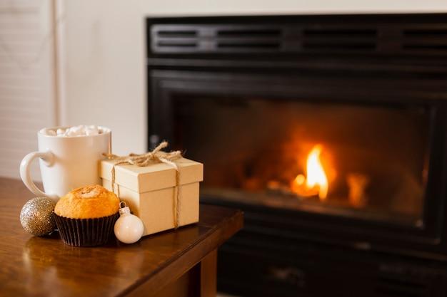 Arrangement avec boîte cadeau près de la cheminée