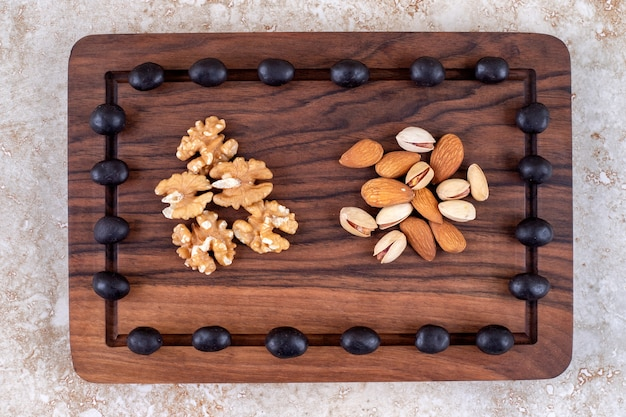 Un arrangement de bonbons au chocolat et de piles de noix sur une planche
