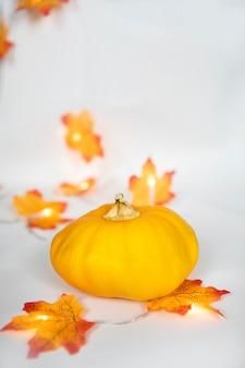 Arrangement de bordure d'automne de citrouille orange et de feuilles colorées avec bokeh allume un b blanc cassé
