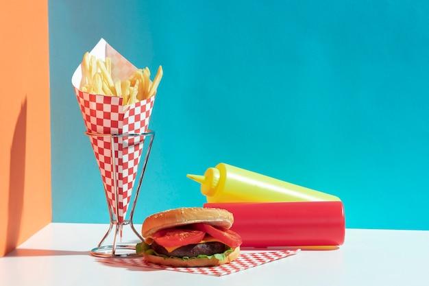 Arrangement avec des bouteilles de sauce et un hamburger