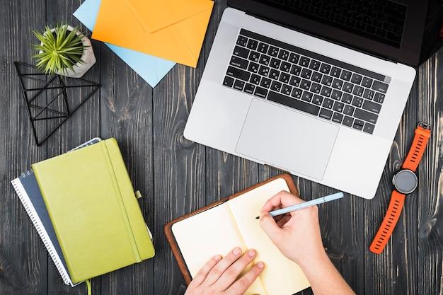 Arrangement de bureau vue de dessus avec une personne écrivant