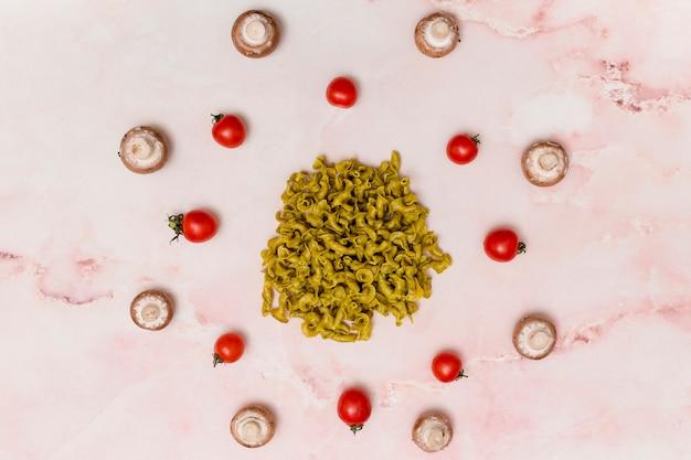 Arrangement circulaire de pâtes crues vertes; tomates rouges; et champignons sur la surface de marbre