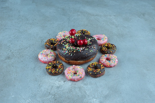 Arrangement de collations de beignets autour d'un gros beignet sur marbre.