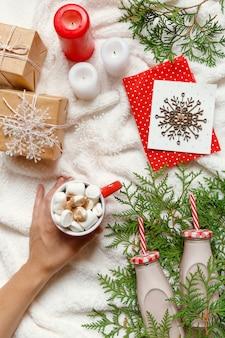 Arrangement confortable festif de noël et du nouvel an, les mains de la femme tiennent une tasse de cacao ou de chocolat
