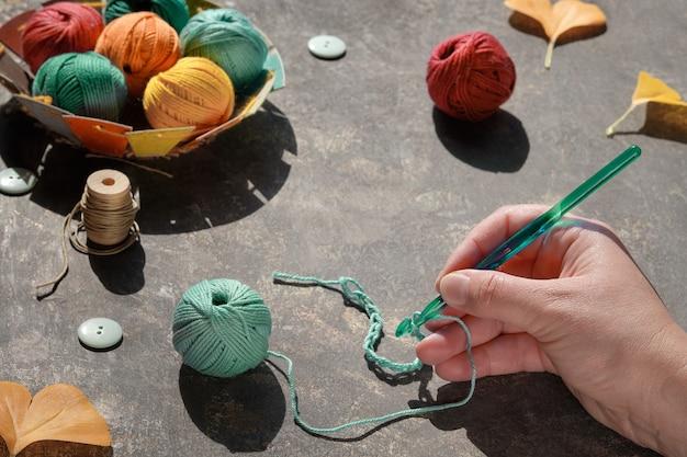 Arrangement créatif de matériaux d'artisanat pour le tricot et le crochet sur une table sombre.