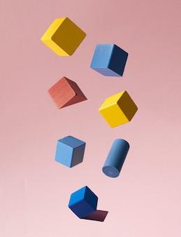 Arrangement créatif avec des objets géométriques en bois colorés sur fond rose pastel