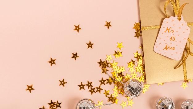 Arrangement créatif pour une fête de quinceañera avec des étoiles dorées et un cadeau