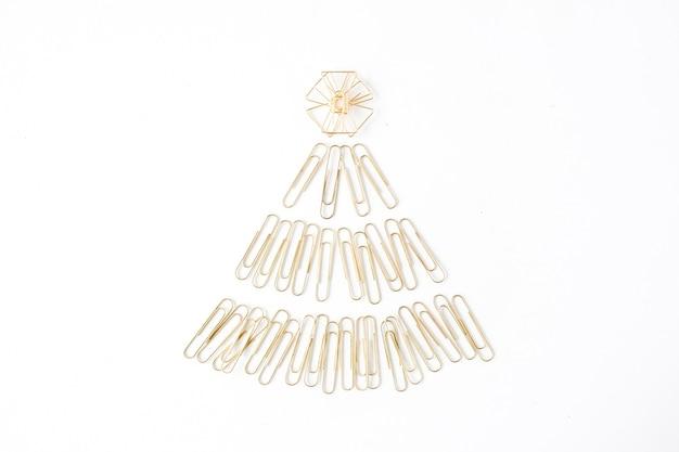 Arrangement créatif de sapin de noël doré brillant composé de clips sur fond blanc.
