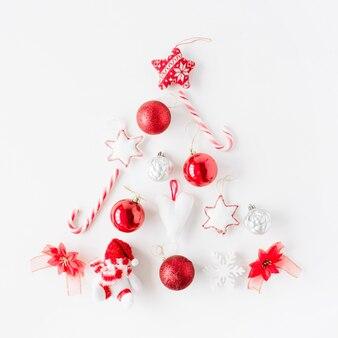 Arrangement créatif de sapin de noël rouge vif fait de boule de noël, bonbons, jouets sur blanc