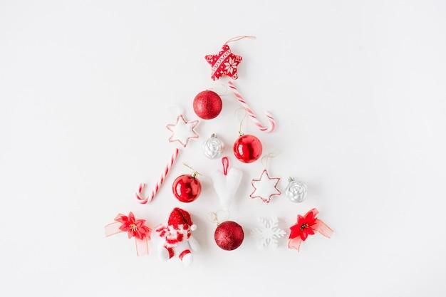 Arrangement créatif de sapin de noël rouge vif fait de boule de noël, bonbons, jouets sur fond blanc.