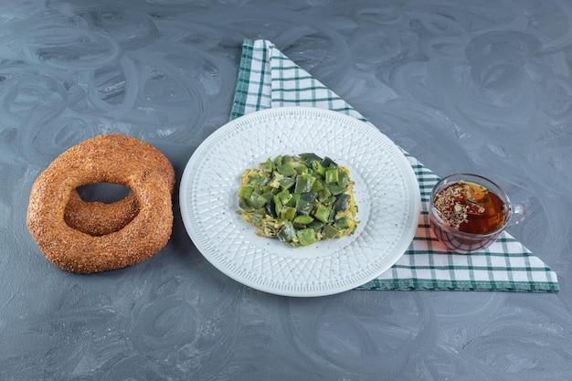 Arrangement de déjeuner sur nappe pliée sur table en marbre.