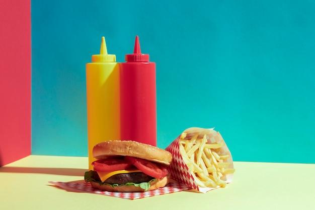 Arrangement avec de délicieux burger et des bouteilles de sauce
