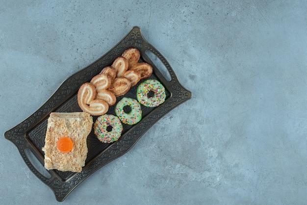 Arrangement de dessert avec des biscuits feuilletés, une tranche de gâteau, un beignet et sur un plateau orné sur une surface en marbre