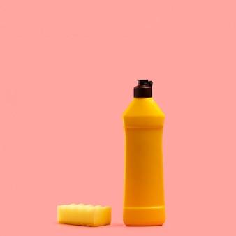 Arrangement avec un détergent jaune et une éponge