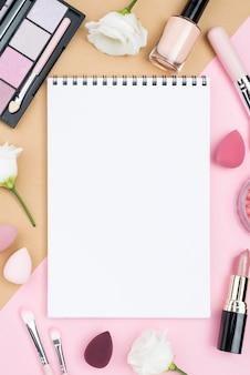 Arrangement de différents produits de beauté avec bloc-notes vide