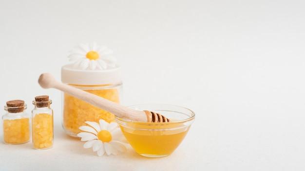Arrangement avec du miel et des sels sur fond blanc