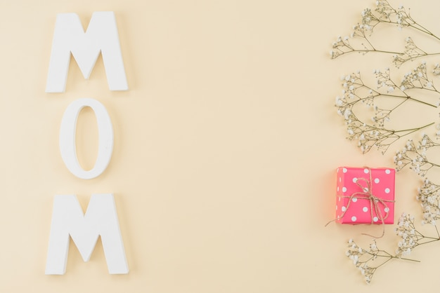 Arrangement du mot maman, gypsophilie et boîte à cadeaux