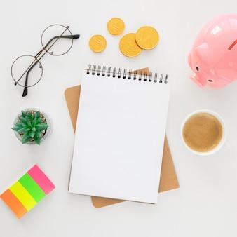 Arrangement d'éléments financiers vue de dessus avec bloc-notes vide