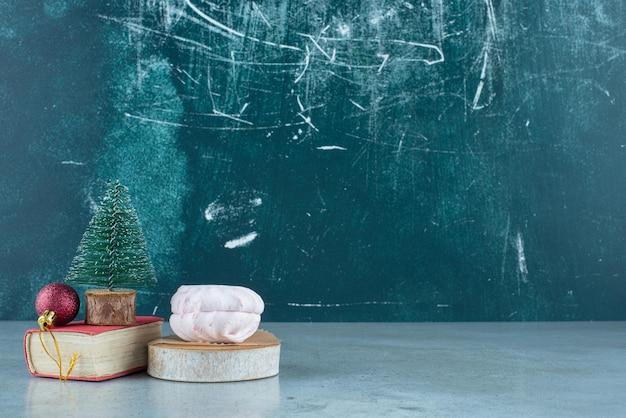 Arrangement festif d'une boule, d'une figurine d'arbre sur un petit livre et de biscuits empilés sur du marbre.