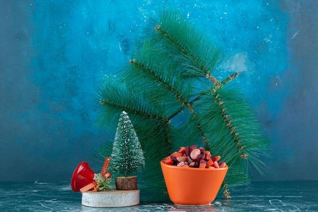 Arrangement festif de saladier et décorations sur bleu.