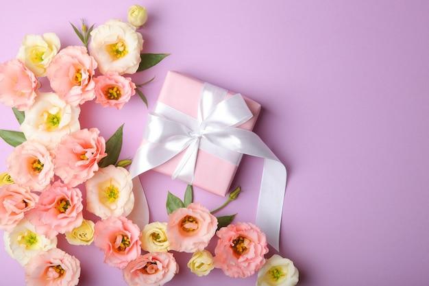 Arrangement de fleurs et cadeau sur fond coloré vue de dessus avec place pour le texte