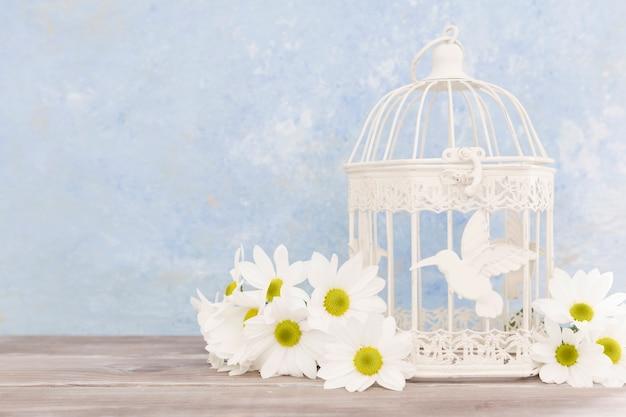Arrangement avec des fleurs et une cage à oiseaux