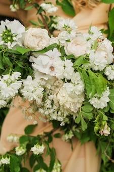 Arrangement de fleurs de fleurs blanches sur la robe. mariée tient un bouquet de mariage