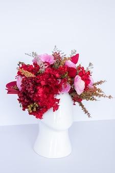 Arrangement de fleurs avec des fleurs rouges séchées avec pot en forme de tête