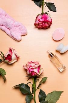 Arrangement de fleurs roses et outils de beauté et traitement, vue de dessus avec espace