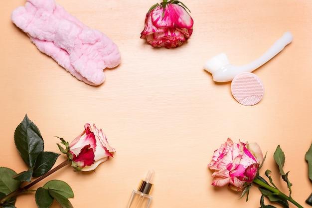 Arrangement de fleurs roses et outils de beauté et vue de dessus de traitement