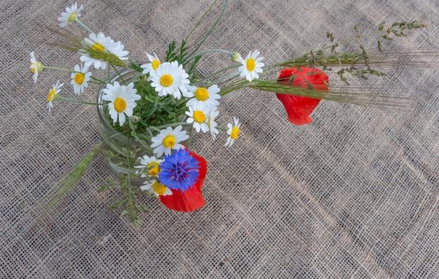 Arrangement floral de coquelicots rouges marguerites bleuets et fleurs sauvages sur fond de toile de jute