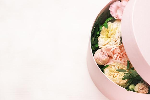 Un arrangement floral élégant et délicat dans une boîte ronde de chapeau sur le fond rose avec copie espace