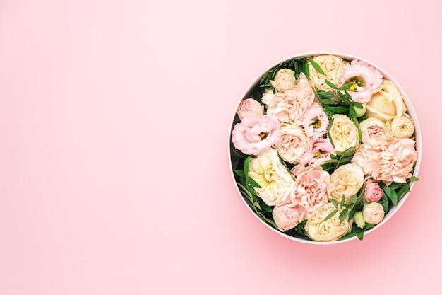 Un arrangement floral élégant et délicat dans une boîte ronde de chapeau sur le fond rose avec espace de copie. coffret cadeau pour le 8 mars, journée internationale de la femme, fête des mères, saint valentin, anniversaire,
