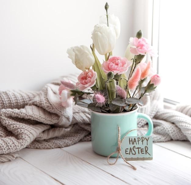 Arrangement floral de pâques avec des fleurs naturelles et l'inscription joyeuses pâques sur la carte.