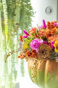 Arrangement floral de roses à l'intérieur de la citrouille décorée pour un halloween différent