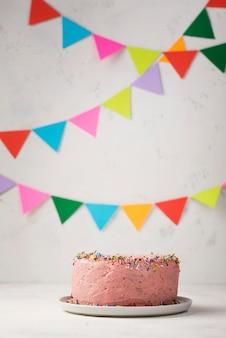 Arrangement avec gâteau rose et décorations