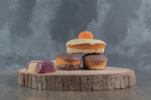 Un arrangement de gâteaux et marmelades sur une planche de bois