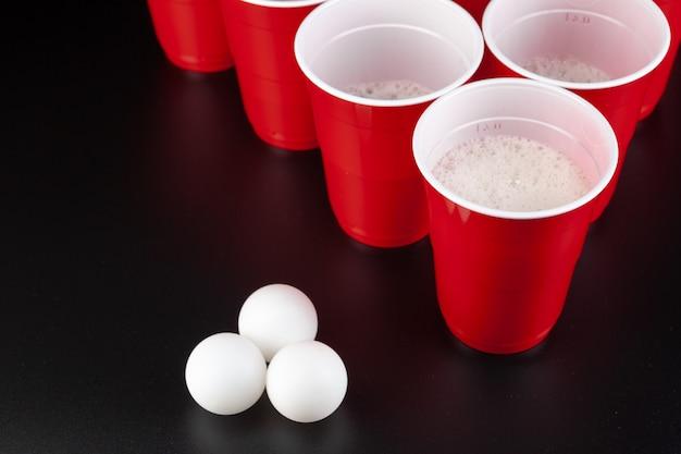 L'arrangement des gobelets en plastique rouge pour le jeu de bière pong