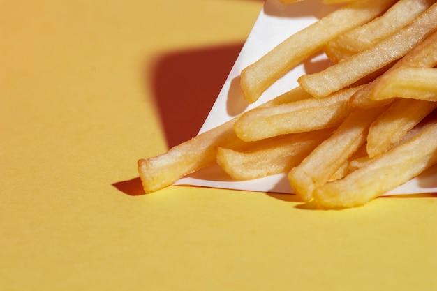 Arrangement grand angle avec des pommes de terre frites sur fond jaune