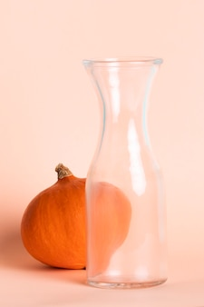 Arrangement avec grand verre vide et citrouille