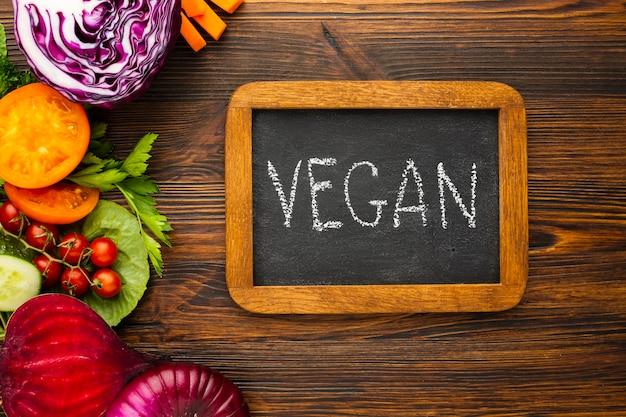 Arrangement de légumes plat lay avec lettrage végétalien sur tableau noir