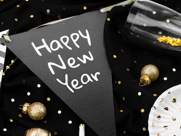 Arrangement de lettrage de nouvel an avec des décorations dorées