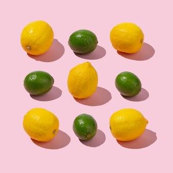 Arrangement de limes et citrons sur fond rose pastel