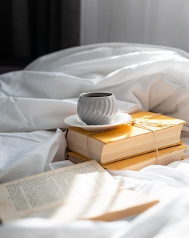 Arrangement avec livres et tasse au lit